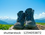 hiking boots and mountains... | Shutterstock . vector #1254053872