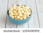 popcorn in blue cup on white... | Shutterstock . vector #1254330592