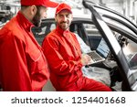 two male auto mechanics in red... | Shutterstock . vector #1254401668
