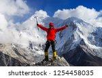 girl climber raises hands on...   Shutterstock . vector #1254458035