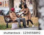 Young Woman Giving Food To...