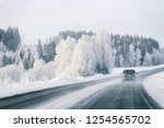 a car at a road in snowy winter ... | Shutterstock . vector #1254565702