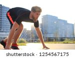 sporty young man in start... | Shutterstock . vector #1254567175