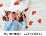 couple kisses lying on a floor... | Shutterstock . vector #1254640582