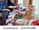 the hands of women taking food... | Shutterstock . vector #1254723388
