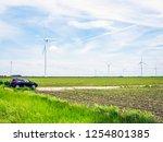 a car parked near a wind... | Shutterstock . vector #1254801385