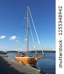 a wooden sailboat docked at... | Shutterstock . vector #1255348942