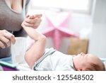 mother changing a tiny newborn... | Shutterstock . vector #125548502