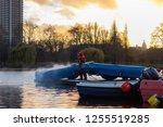 red suited dock worker cleaning ... | Shutterstock . vector #1255519285