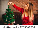 smiling blonde woman decorating ... | Shutterstock . vector #1255569958
