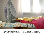 iron on the ironing board with... | Shutterstock . vector #1255584892