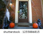 Small photo of Two Pumpkins Reside on the Doorstep of a Brick Townhouse Beckoning Visitors to the Front Door Filled with Skeleton Spook Decorations, Flanked by Cobwebs and a White Ghost in the Bushes