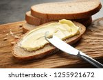 spreading butter onto toast... | Shutterstock . vector #1255921672