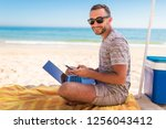 happy man using a smart phone... | Shutterstock . vector #1256043412