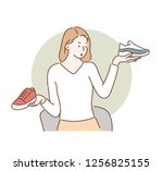 a woman is picking up two shoes ... | Shutterstock .eps vector #1256825155