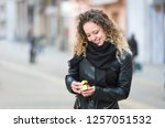 young woman opening a gift box... | Shutterstock . vector #1257051532