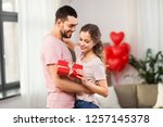 Stock photo valentines day relationships and people concept happy couple with gift box hugging at home 1257145378