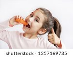 cute little girl eating carrot. ... | Shutterstock . vector #1257169735