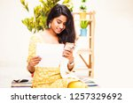 young indian woman paying bills ... | Shutterstock . vector #1257329692