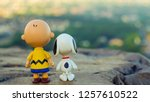 Small photo of Songkhla, Thailand - November 30, 2018: Happy Holidays! Snoopy and Charlie Brown plastic toys Standing looking at mountain.. The morning before Xmas.