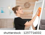 young chambermaid wiping mirror ... | Shutterstock . vector #1257716032