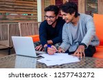 Small photo of Indian young business people businessman freelancer working outdoors chaise lounge on the beach with laptop.two successful friends freelancing surfing remote work summer vacation in tropical paradise.