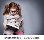 Little Smart Girl Holding A...