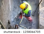 Small photo of Worker demolish old concrete wall with jackhammer
