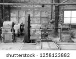 Industrial lathe of the first half of the 20th century. The workshop is located in an old mercury mine, now a museum, in Abbadia San Salvatore, in Italy. Black and white picture.