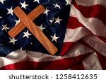 Small photo of Evangelical America, christianity, born again christian and fundamentalist religious right concept with close up on a wooden cross or crucifix on the american flag with dramatic light and moody tone