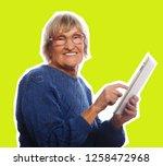 senior happy woman using ipad ... | Shutterstock . vector #1258472968