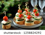 Stock photo canape with salted herring cucumber boiled potatoes and cherry tomato on rye croutons christmas 1258824292