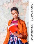 Small photo of Young African American Woman reading book, listening music outside in New York, wearing fashionable orange red jacket, skit, blue earphone, hands holding red book, standing by painted wall on street.