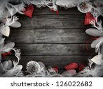 Valentines design - Love wreath with copyspace on wooden background. Valentines ornaments on wood with hearts and ribbons. - stock photo