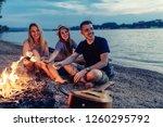 friends sitting around a fire... | Shutterstock . vector #1260295792