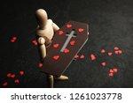 offin in hands of wooden man.... | Shutterstock . vector #1261023778