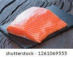 fresh salmon fillet on black... | Shutterstock . vector #1261069555