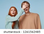 Small photo of A guy and a girl isolated on a blue background. The girl looks into the camera. Scaredly shocked, she closes the guy's eyes with her palm, as if she sees something indecent, immoral and propriety.