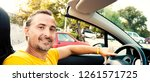 handsome man driving... | Shutterstock . vector #1261571725