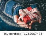 hands holding little gift with... | Shutterstock . vector #1262067475