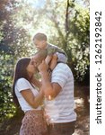 mom kissing dad with kid on his ... | Shutterstock . vector #1262192842