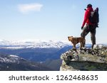 Man And Dog Standing On Steep...