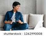 smiling young asian man sitting ... | Shutterstock . vector #1262990008