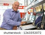 mature man shopping for laptop... | Shutterstock . vector #1263352072