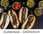 Hot dogs or brats in buns on a wooden table