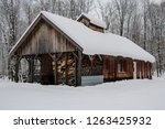 A maple syrup sugar shack in rural Quebec covered in snow.