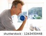mature man exercising at home... | Shutterstock . vector #1263450448