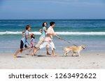 family exercising pet dog... | Shutterstock . vector #1263492622