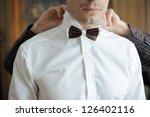 groomsman helping groom to put...   Shutterstock . vector #126402116