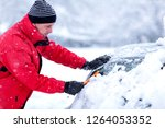 young man removing snow from... | Shutterstock . vector #1264053352